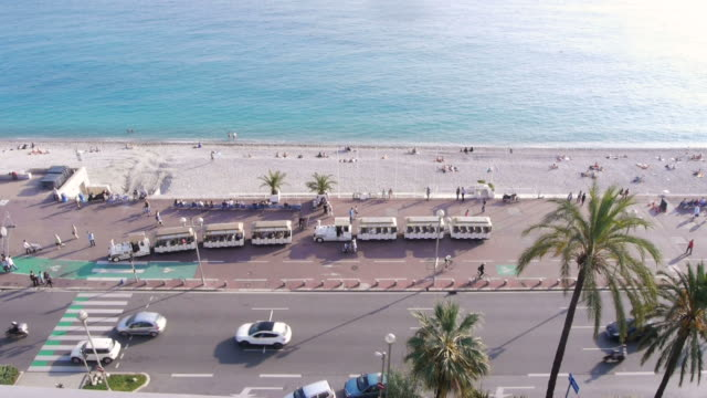 w/s, promenade des anglais, mediterranean sea, azur, beach, palm trees, tourist train arriving, rooftop view, nice, france - promenade stock videos & royalty-free footage