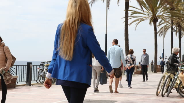 Promenade of Marbella in Andalusia in Spain the road is lined with palm trees people are passing by