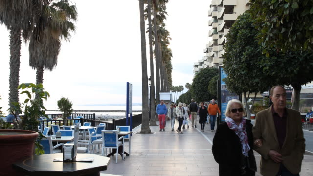 Promenade of Marbella in Andalusia in Spain the road is lined with palm trees people are passing by at sunset