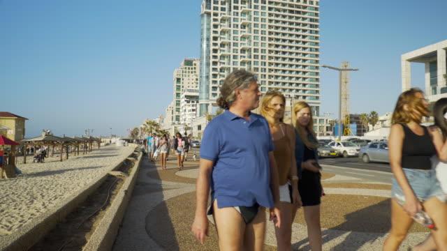 TEL AVIV: Promenade of Tel Aviv beach with people passing by.