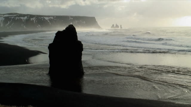 zo ws promontory stack and beach of black lava sand dyrholaey, vik, iceland - oceano atlantico del nord video stock e b–roll