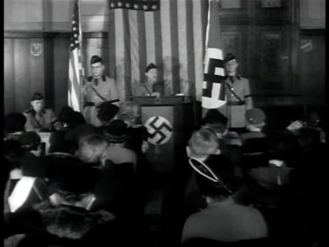 pronazi germanamerican bund meeting w/ speaker behind podium vs young adult males standing by nazi flags angled ws audience listening speaker shaking... - nordeuropäischer abstammung stock-videos und b-roll-filmmaterial
