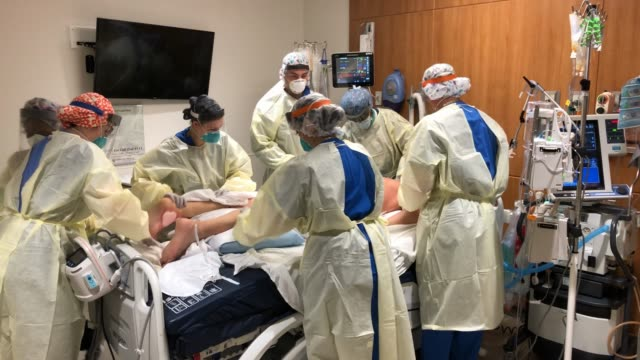 """prone team,"""" wearing personal protective equipment , turns a covid-19 patient onto his stomach in a stamford hospital intensive care unit , during... - belly stock videos & royalty-free footage"""