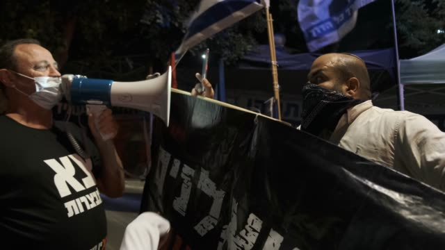 """vidéos et rushes de pro-netanyahu counter-protester holds a banner which reads """"leftists are traitors"""" as he confronts an anti-netanyahu protester using a bullhorn... - homme politique"""