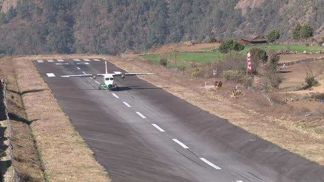 ms ts prop aircraft flying and landing on small runway of lukla airport near khumbu valley / lukla, khumbu region, nepal - khumbu stock videos and b-roll footage