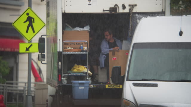 A prop master on a motion picture set works inside a box truck during a rainstorm.