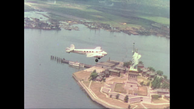 1937 prop plane flies above the new york city skyline - statue of liberty new york city stock videos & royalty-free footage
