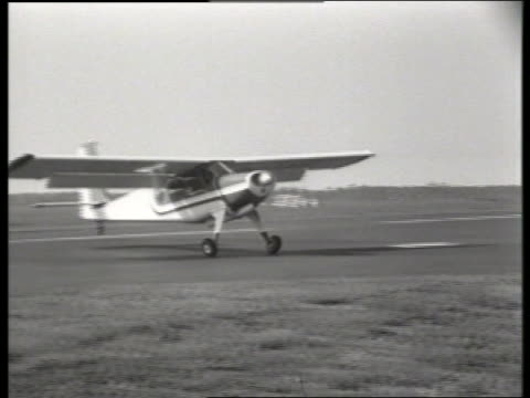 b/w pan of propeller airplane taking off from runway / piper cub plane / teterboro, nj / no sound - propeller aeroplane stock videos & royalty-free footage