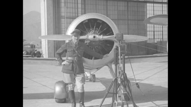 propeller and motor on plane nose / pilot roscoe turner stands in front of plane, microphones on tripods to side, building in bg / plane taxiing,... - バーバンク点の映像素材/bロール