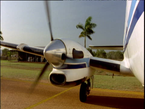 propeller on wing of small plane starts up moves into full powered revolutions palm trees and grass in background australia - propeller video stock e b–roll