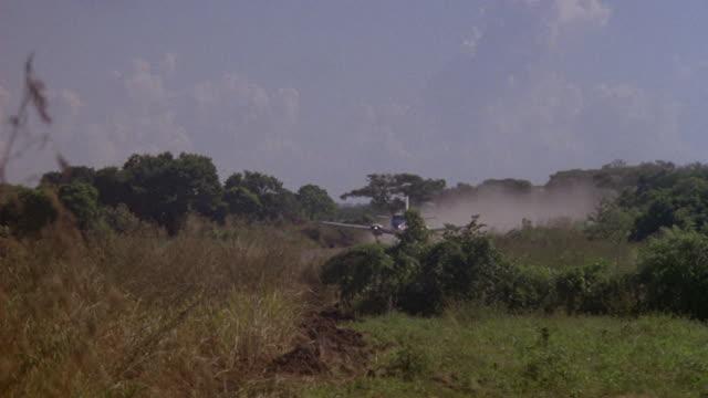 stockvideo's en b-roll-footage met a propeller plane lands on a runway in a colombian field. - start en landingsbaan