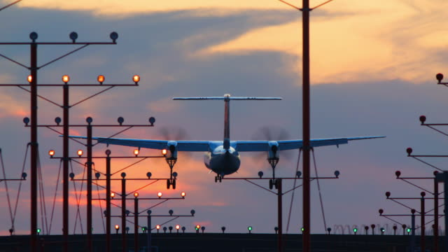 Propeller-driven airplane lands at sunset against richly textured sky, landing lights in foreground: Bombardier Q-400