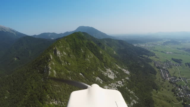 ld propellers on the plane slowly turning while flying along a forest covered mountain ridge in sunshine - propeller stock videos & royalty-free footage