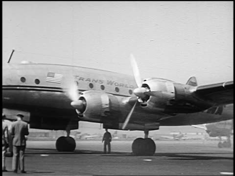 b/w 1951 propellers on twa constellation starting to spin / two men in uniforms in foreground - twa video stock e b–roll