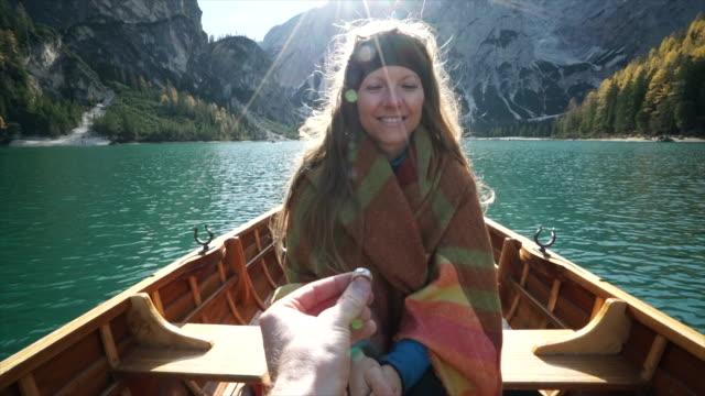 vídeos de stock e filmes b-roll de proposing to woman on boat on alpine lake at sunrise - surpresa