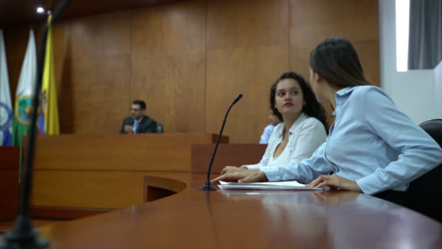 Prosecutor and client at the courtroom talking during the trial
