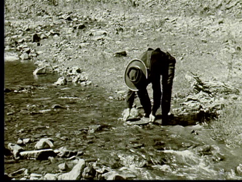 1924 B/W WS Prospector panning for gold in stream / South Dakota, USA