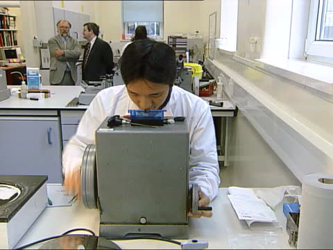 cltn sue england london int women working in laboratory woman working at equipment in laboratory shaving thin slices of tissue to be examined under a... - film tilt stock videos & royalty-free footage