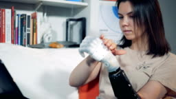 Prosthetic hand is being regulated by a lady and used for typing