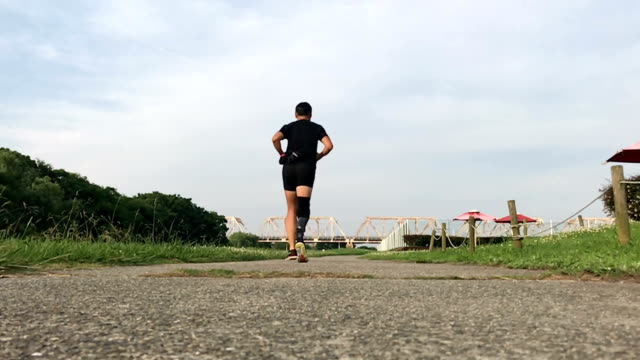 prosthetic legged japanese man running in a park - artificial limb stock videos & royalty-free footage