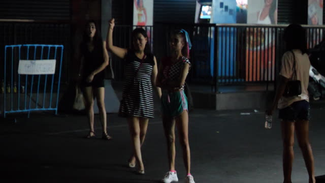 prostitutes stand across the street from nana plaza. bars, restaurants and businesses are closed in entertainment districts after the bangkok... - thailand stock videos & royalty-free footage