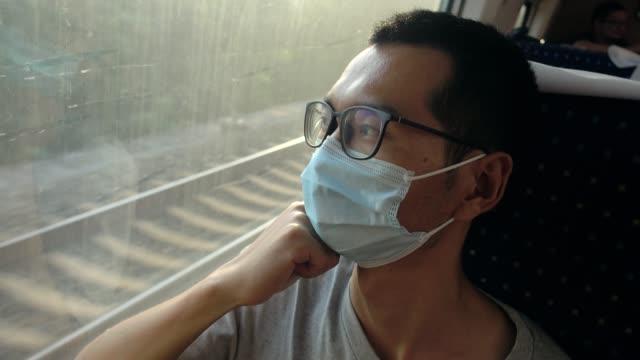 schutz während der reise,mann trägt gesichtsmaske im zug - tourism stock-videos und b-roll-filmmaterial