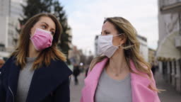 Protection.Two young women with pollution masks  walking down the street