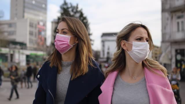 vidéos et rushes de protection.deux jeunes femmes avec des masques de pollution marchant dans la rue - parler