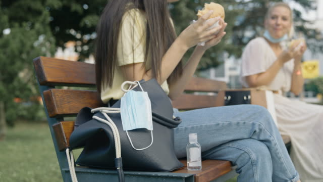slo mo protective face mask hanging from the purse in front of friends eating hamburger on the bench in public park - bench stock videos & royalty-free footage