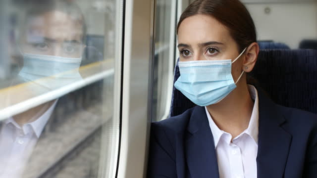 protective mask worn on a train. young woman on a journey. - train vehicle stock videos & royalty-free footage