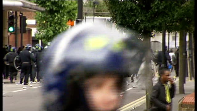 protest against plans to use water cannon in london t08081148 / tx ext back view riot police officers running along street as hooded youth throws... - water cannon stock videos and b-roll footage
