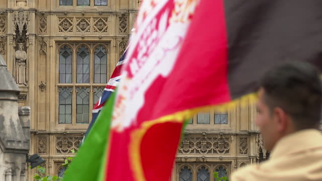 protest outside the houses of parliament over the taliban takeover in afghanistan - national flag stock videos & royalty-free footage