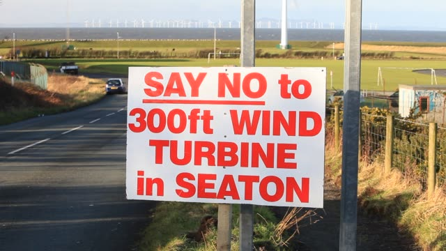 protest sign about a new wind turbine in seaton near workington, cumbria, uk. - roadside stock videos & royalty-free footage