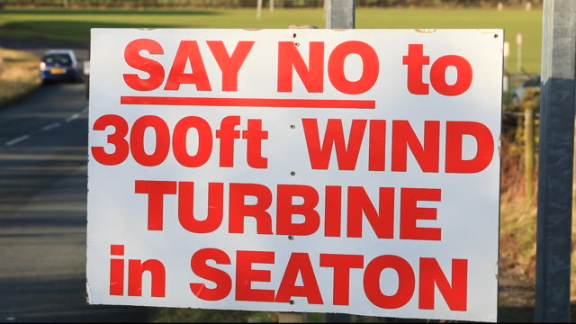 a protest sign about a new wind turbine in seaton near workington, cumbria, uk, with onshore wind turbines and the offshore robin rigg wind farm visible. - power in nature stock videos & royalty-free footage