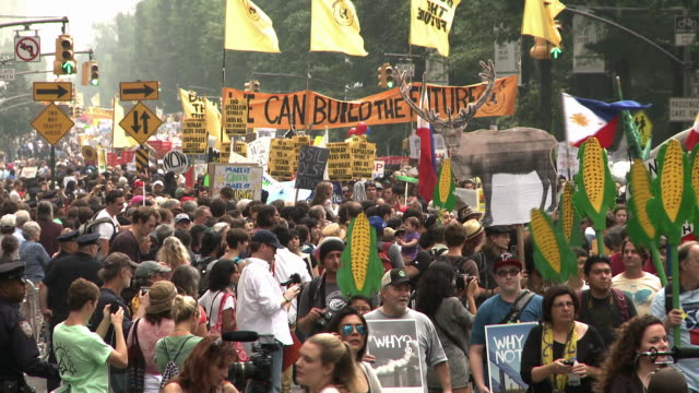 / protest signage such as one that reads Save the environment humans needs over corporate greed