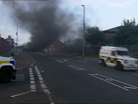 protestant demonstrators clash with police in belfast riot police vehicles along road with smoke from fire smouldering in local residents stood... - protestantism stock videos & royalty-free footage