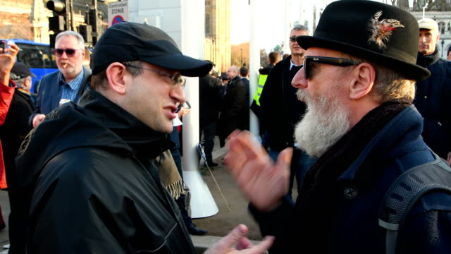 a protester and counterprotester have a discussion as they attend a demonstration in parliament square against antisemitism in the labour party on... - soziale gerechtigkeit stock-videos und b-roll-filmmaterial