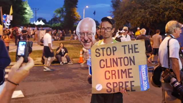 a protester holding an image of bernie sanders holds a sign reading stop the clinton crime spree near the entrance to the democratic national... - 2016 stock-videos und b-roll-filmmaterial