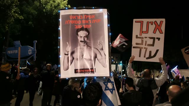 """protester holds a placard bearing the figure of sacha baron cohen and a writing which reads """"even borat can be a better prime minister"""" during a... - sacha baron cohen stock-videos und b-roll-filmmaterial"""