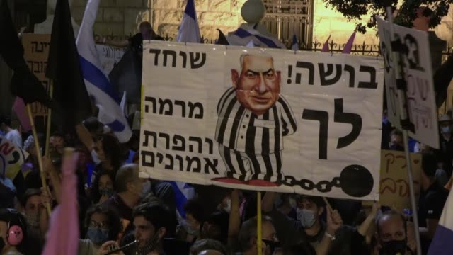 protester holds a placard bearing the image of netanyahu in prison uniform during a mass demonstration in front of prime minister benjamin... - israel stock videos & royalty-free footage
