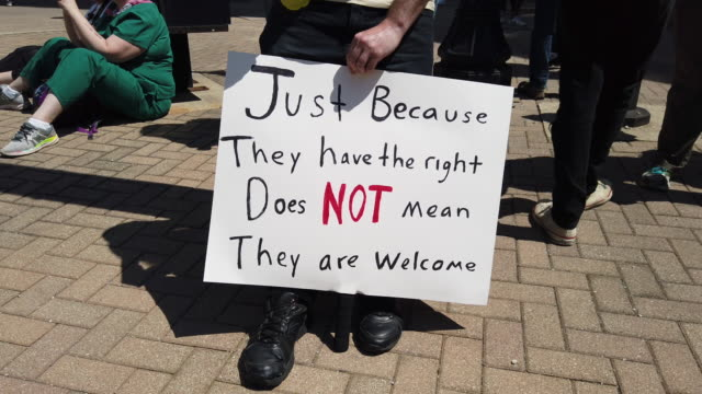 a protester holds a sign reading just because they have the right does not mean they are welcome while protesting the kkk hundreds of counter... - ku klux klan stock videos and b-roll footage