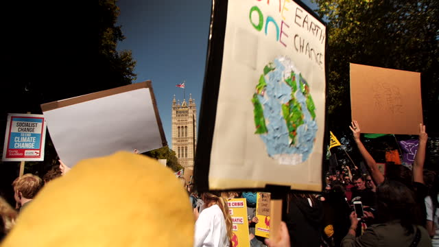 "protester holds a sign that reads ""one earth one chance"" during a climate change protest in victoria tower gardens, london. - environment or natural disaster or climate change or earthquake or hurricane or extreme weather or oil spill or volcano or tornado or flooding stock videos & royalty-free footage"