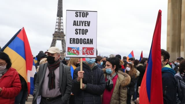 """protester holds a sign that reads """"stop aliyev, stop erdogan"""" the eiffel tower in the background during a demonstration organized by the cooperation... - osteuropäische kultur stock-videos und b-roll-filmmaterial"""