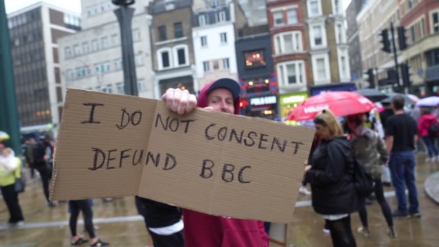 protester holds a sign to defund the bbc on august 15, 2020 in london, england at no new normal march that protest against government restriction,... - bbc bildbanksvideor och videomaterial från bakom kulisserna