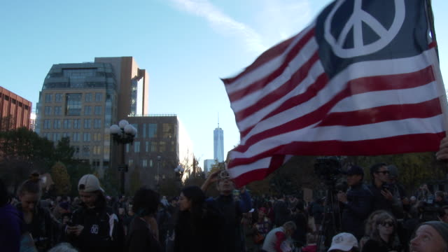 A protester holds up an American Flag with a Peace Sign on it at an AntiDonald Trump rally in Washington Square Park NYC The Freedom Tower is visible...