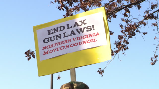 Protester Holds Up Signs to End Lax Gun Laws at The Nation's Gun Show at the Dulles Expo Center on December 28 2012 in Dulles Virginia