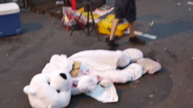 protester in a guy fawkes mask, and holding a peace sign walks past a person dressed in a polar bear outfit covered in fake blood near the entrance... - fake stock videos & royalty-free footage