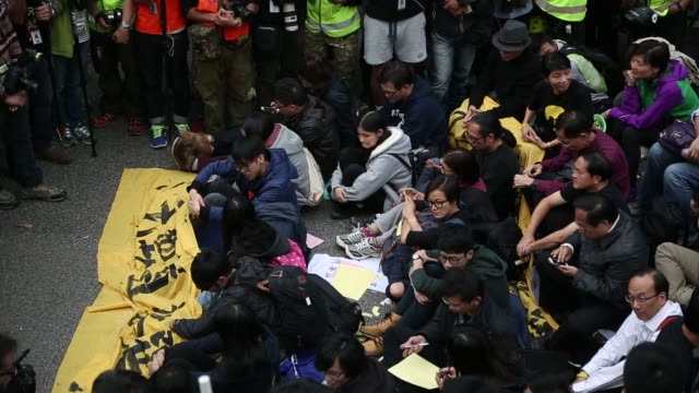 vídeos y material grabado en eventos de stock de a protester is carried by police officers near the central government offices in the admiralty district of hong kong china protesters sit on the... - 2014