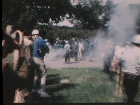 protester kicks a smoking tear gas dispenser into a crowd of people during the 1968 democratic convention in chicago. - 1968 stock-videos und b-roll-filmmaterial