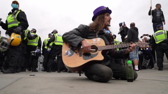 a protester plays the guitar as protesters clash with police officers during a we do not consent antilockdown rally at trafalgar square on september... - guitar stock videos & royalty-free footage